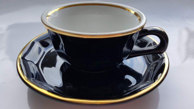 Merkloos. Koffie kop en schotel. Zwart wit met gouden rand. Per set 1