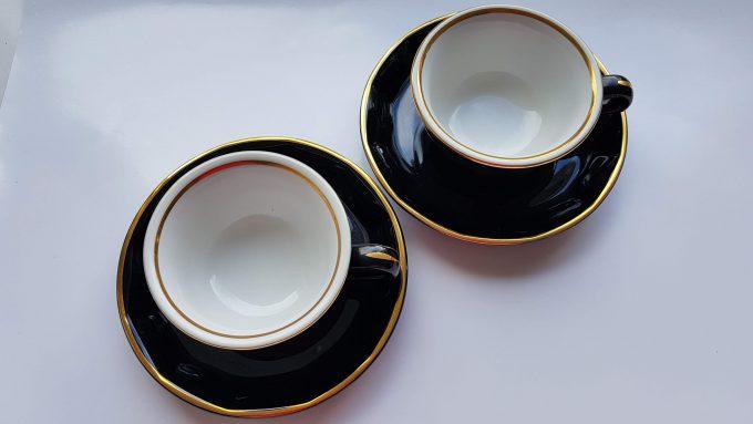 Merkloos. Koffie kop en schotel. Zwart wit met gouden rand. Per set 3
