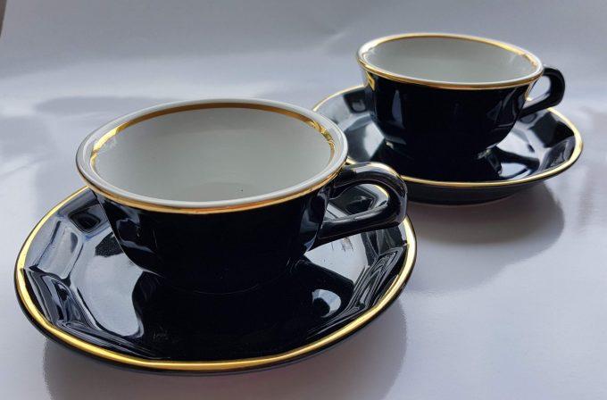 Merkloos. Koffie kop en schotel. Zwart wit met gouden rand. Per set 2