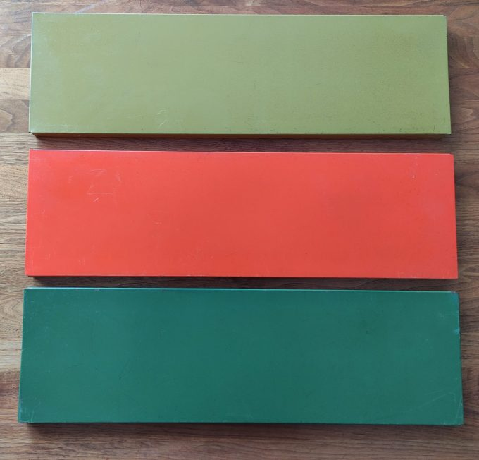 Tomado. Ontwerp Adriaan Dekker ca 1958. Boekenrek met 2 staanders zwart en drie planken. Oranje, Lichtgroen, Donkergroen. 2