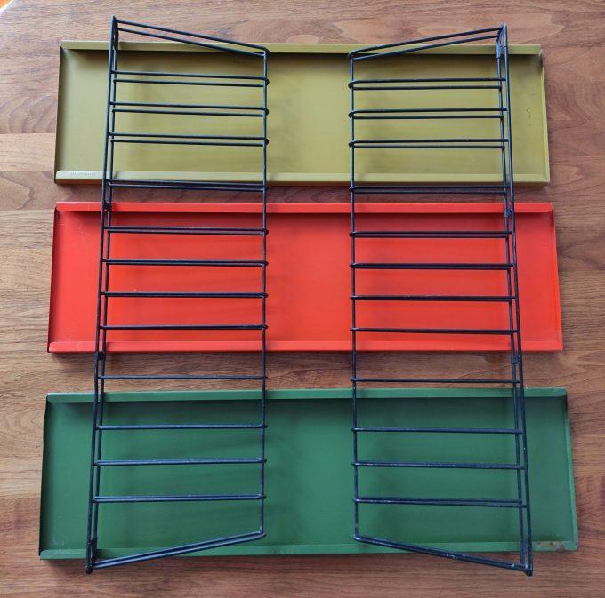 Tomado. Ontwerp Adriaan Dekker ca 1958. Boekenrek met 2 staanders zwart en drie planken. Oranje, Lichtgroen, Donkergroen. 1